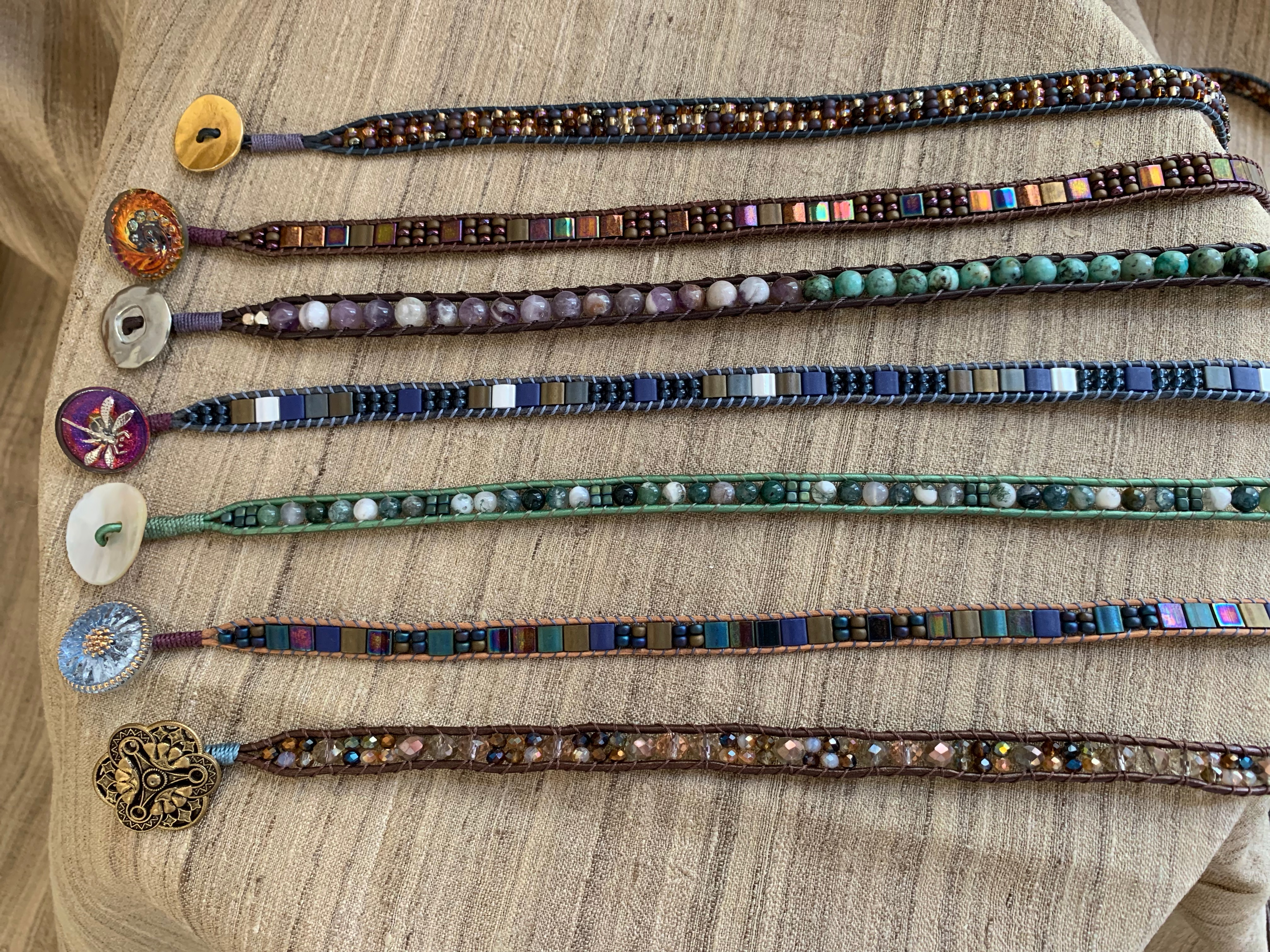 Several handmade beaded bracelets lined up side by side, each with different colors.